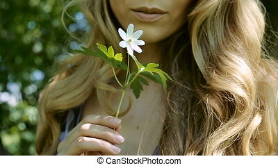 young woman smelling brings it to his lips white flower -...
