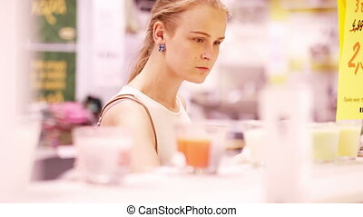 Young woman smelling scented candles - Young blond woman...