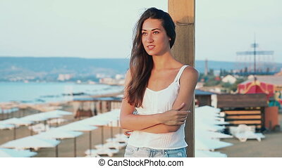 Young woman smile to dawn at background of the sea beach