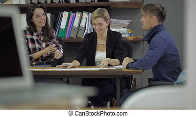 Young woman smiling and gesturing, explaining something to a girl and a guy