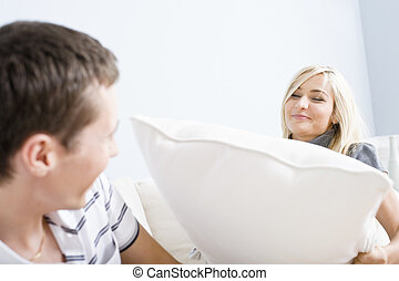 Young Woman Smiling and Hitting Young Man With Pillow