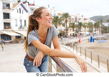 Young woman smiling and leaning on railing at the beach