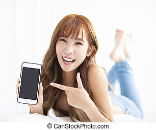 young woman smiling and showing smart phone while lying on the bed