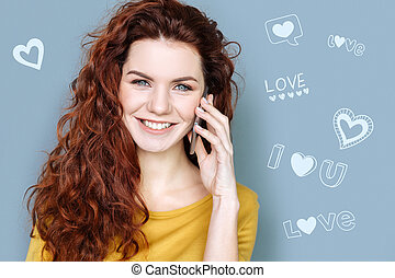 Young woman smiling and talking on the phone with her boyfriend