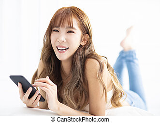 young woman smiling and using smart phone while lying on the bed