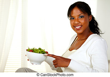 Young woman smiling at you pointing salad