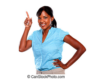 Young woman smiling at you pointing up - copyspace