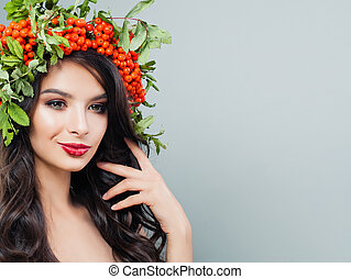 Young woman smiling. Brunette girl with makeup, healthy wavy hair, red berries and green leaves on background with copy space