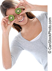 Young woman smiling hiding her eyes with kiwi fruits