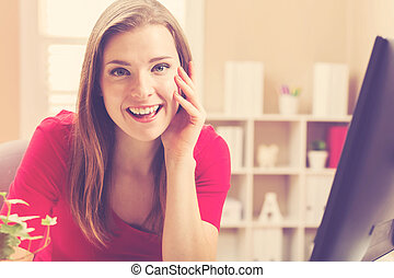 Young woman smiling in her home office