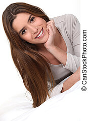 Young woman smiling laid on a bed