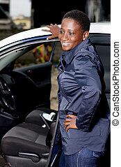 Young woman smiling mechanic standing beside a car.