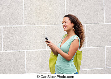 Young woman smiling outdoors with mobile phone