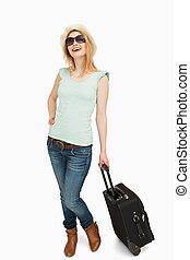 Young woman smiling while holding a suitcase