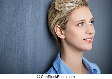 Young Woman Smiling While Looking Away Against Blue Wall