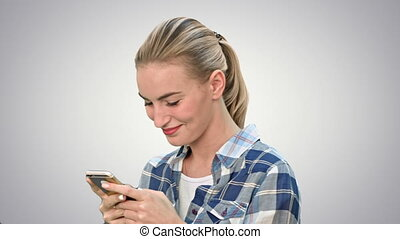 Young woman smiling while texting a message via cell phone on white background.