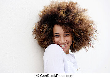 Young woman smiling with afro hair against white background
