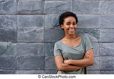 young woman smiling with arms crossed against gray wall