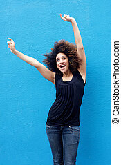 Young woman smiling with arms raised