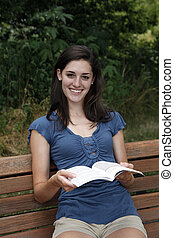 Young woman smiling with book in her hand