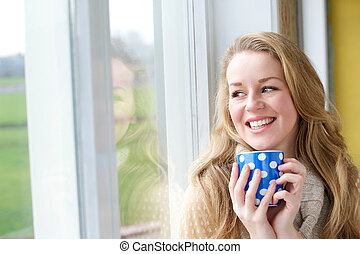 Young woman smiling with cup of tea