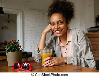 Young woman smiling with glass of fruit juice