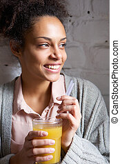 Young woman smiling with glass of orange juice