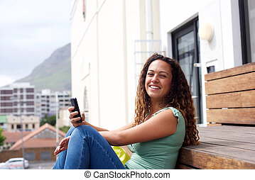 Young woman smiling with mobile phone in the city