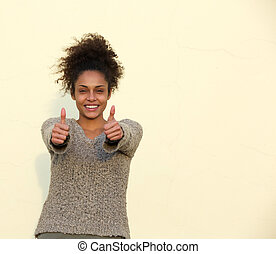 Young woman smiling with thumbs up sign