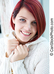 Young woman smiling with white sweater