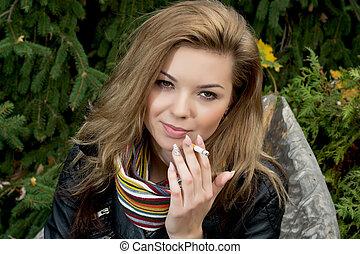 Young woman smokes a cigarette