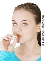 Young woman smoking electronic cigarette (ecigarette),...