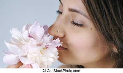 Young woman sniffing pink flower - Young attractive woman...