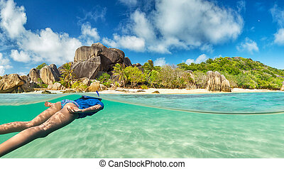 Young woman snorkling on tropical beach. Underwater sports...