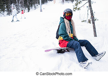 Young woman snowboarder freerider sitting in the mountains on a snowy slope.