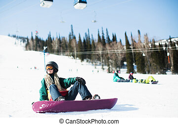 Young woman snowboarder sitting in the mountains on a snowy slope.