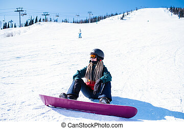 Young woman snowboarder sitting on a snowy slope.