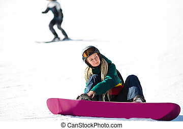 Young woman snowboarder with dreadlocks sitting zipping up his boots while sitting on a snowy slope.