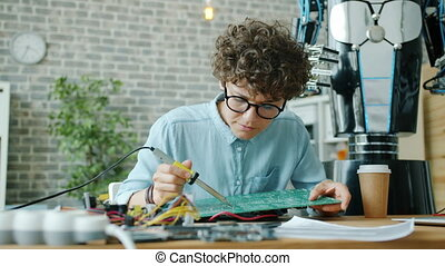 Young woman engineer is soldering microcircuit for droid in office working alone indoors using modern equipment. People, occupation and technology concept.