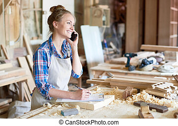 Young Woman Speaking By Smartphone in Modern Joinery -...