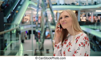 Young woman speaking on phone in mall.