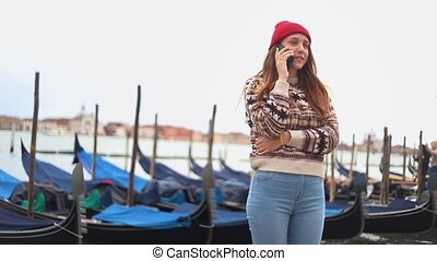 Young woman speaking on the phone staying on the waterfront...