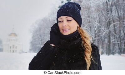 Young woman speaks on the phone in winter park