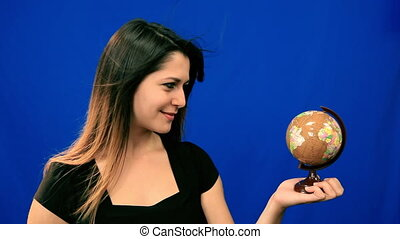 Young woman spinning globe in wind