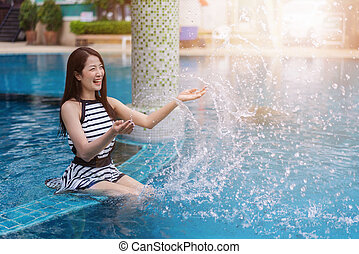 young woman splashing water in swimming pool