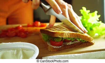 Young woman splitting sandwich with a knife