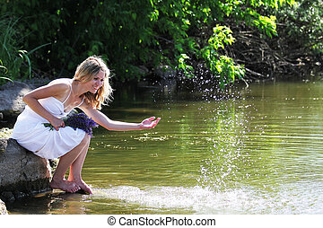 young woman sprinkles water near the lake