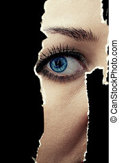 Young woman spying through a hole in the wall - One eye of a...