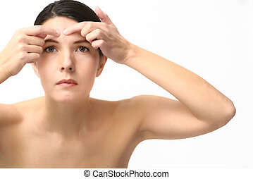 Young woman squeezing a pimple on her forehead
