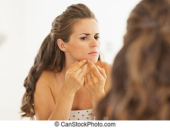 Young woman squeezing acne in bathroom
